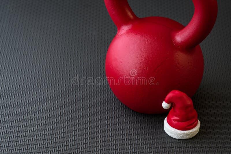 Rode kettlebell op een zwarte gymnastiekvloer met kleine rode en witte Santa Claus-hoed stock afbeeldingen