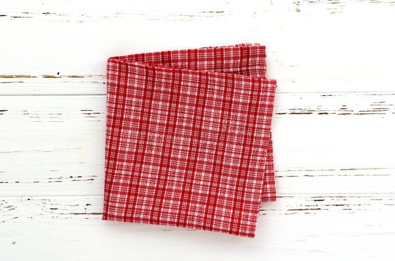 Rode keukendoek op witte uitstekende houten lijst De ruimte van het exemplaar stock foto