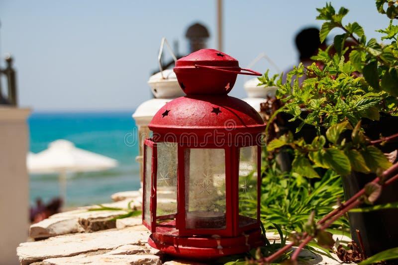 Rode kleine lantaarn als decoratie bij een zeekustrestaurant bekwaam in comfortabele openluchtkoffie met een kleine lantaarn en e stock fotografie