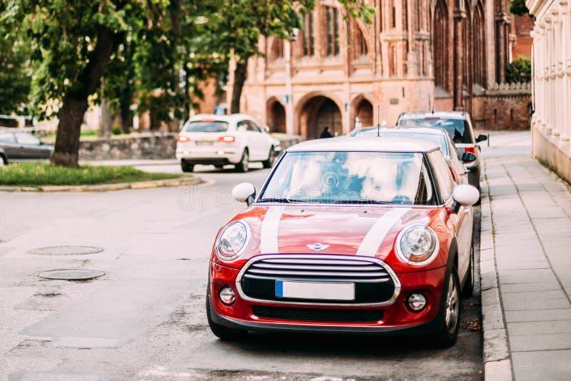 Rode Kleurenauto met Witte Strepen Mini Cooper Parked On Street in Oude Deel Europese Stad stock foto