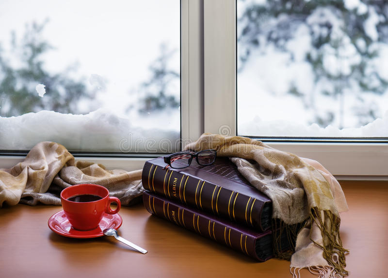 Rode kop van koffie of thee met een metaallepel, fotoalbums en gl stock foto