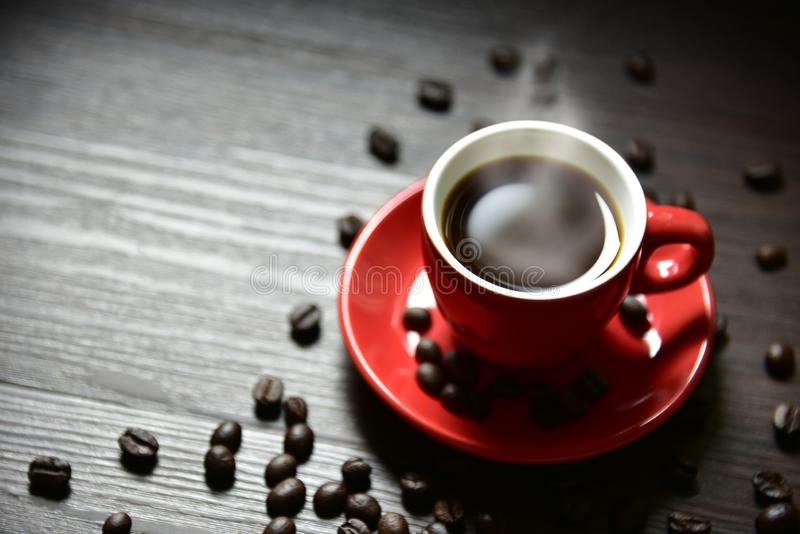 Rode kopkoffie met stroomdamp en koffieboon op houten lijst, selectieve nadruk aangaande rand van kop, het Drinken concept stock foto