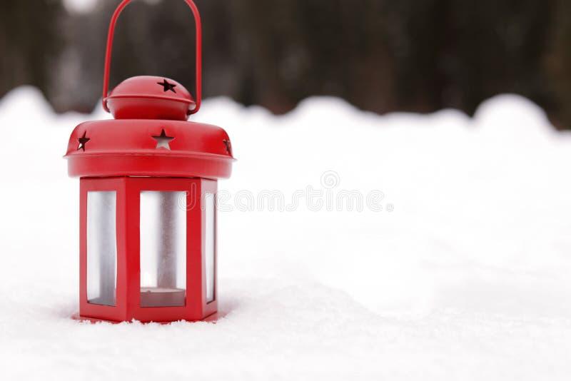 Rode lantaarn met kaars op witte sneeuw in openlucht, ruimte voor tekst stock fotografie
