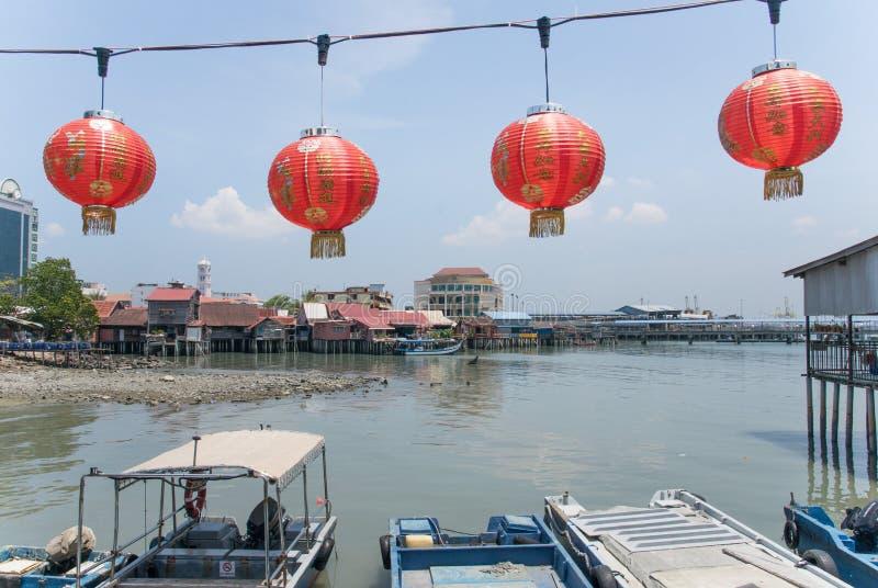 Rode lantaarns die infornt van oceaanmening met houten boten en huizen op de achtergrond in penang Maleisië hangen royalty-vrije stock fotografie