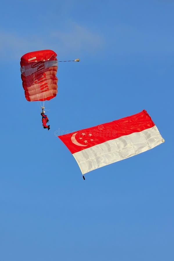 Rode Leeuwen die met de vlag van Singapore parachuteren royalty-vrije stock foto