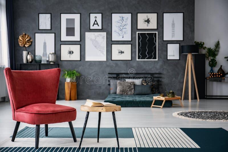 Rode leunstoel naast lijst aangaande tapijt in donker grijs woonkamerbinnenland met galerij op vage achtergrond Echte foto stock afbeelding