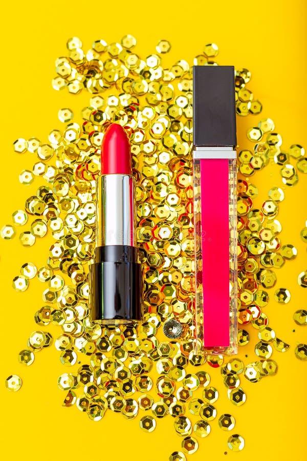 Rode lippenstift en karmozijnrode lipgloss op een gele achtergrond Verti royalty-vrije stock foto's