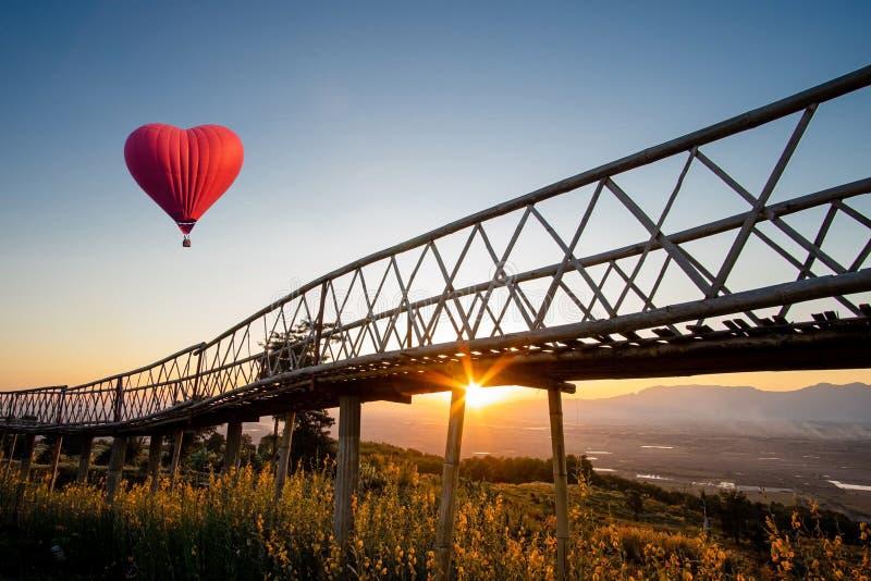 Rode luchtballon in de vorm van een hart boven de zonsondergang bij Ban Doi Sa-ngo Chiangsaen, provincie Chiang Rai, Thailand stock fotografie