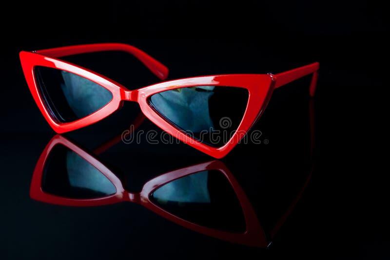 Rode manierzonnebril op een zwarte achtergrond stock afbeelding