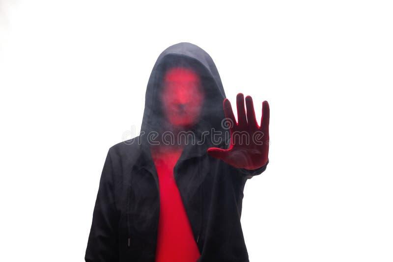 Rode mens in een zwarte kap en een rook die eindeteken tonen Geïsoleerd op wit stock afbeeldingen