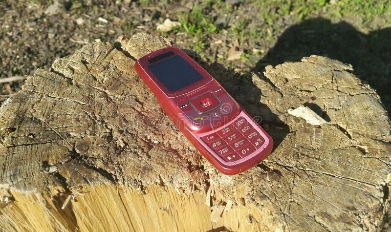 Rode mobiele telefoon2000s rust op een houten stomp royalty-vrije stock afbeelding