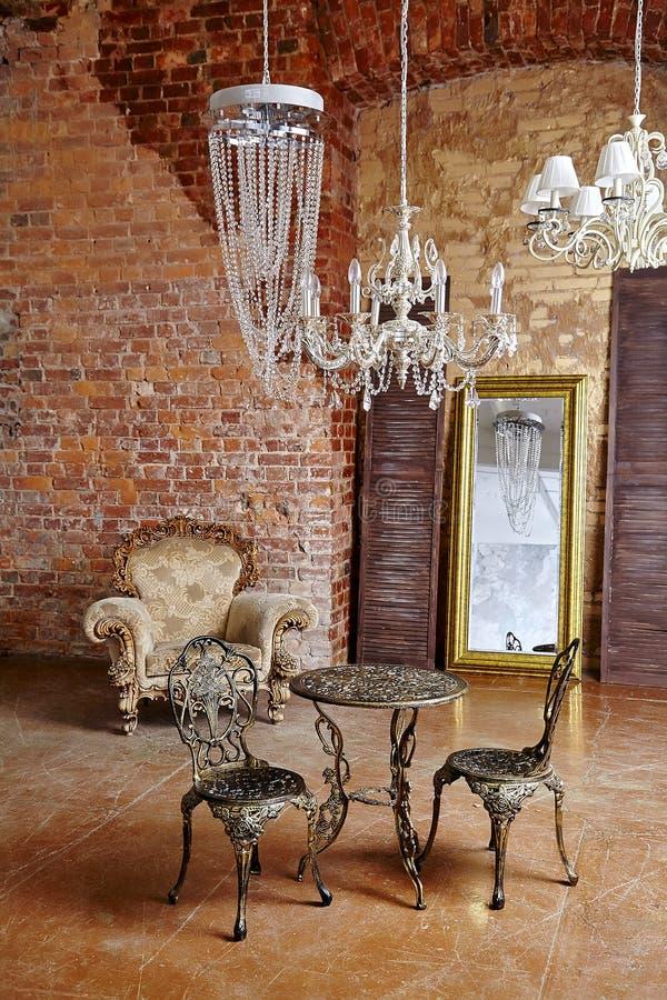 Rode moderne de tegenhangerverlichting van de steenmuur en het moderne concept van het koffietafel binnenlandse bureau stock foto