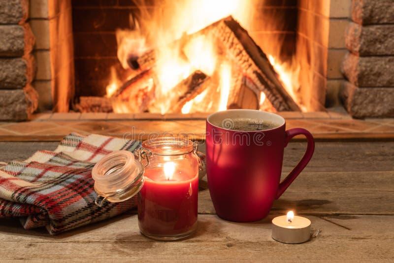 Rode mok met hete thee, en een kaars, wolsjaal, dichtbij comfortabele open haard, in buitenhuis, de wintervakantie royalty-vrije stock fotografie