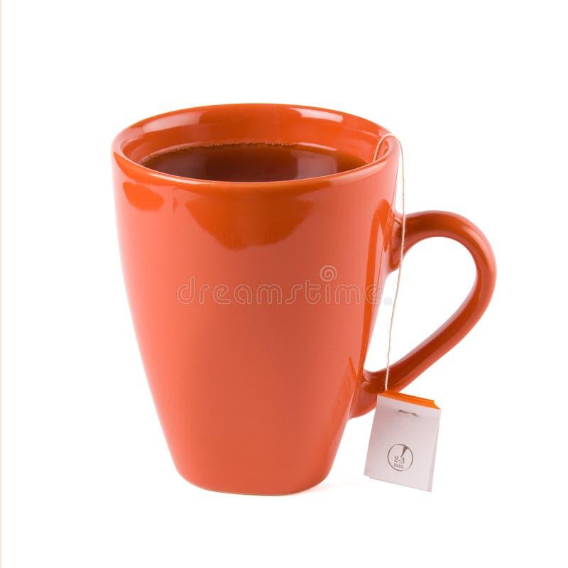 Rode mok met thee en theezakje dat op wit verstand wordt geïsoleerdk stock fotografie
