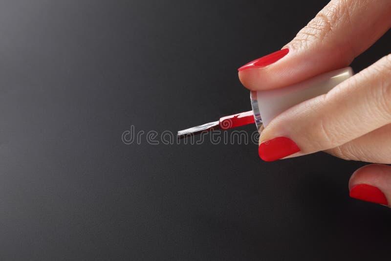 Rode nagellakborstel in vrouwenhand royalty-vrije stock afbeelding