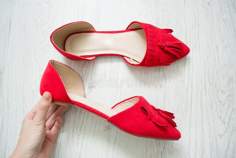 Rode open schoenen in vrouwelijke hand Lichte houten achtergrond Hoogste mening royalty-vrije stock afbeeldingen