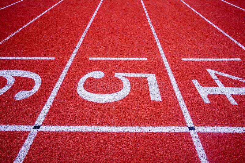 Rode oppervlakte lopende renbaan met wit uit lijnen en aantal in stock afbeelding