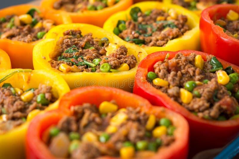 Rode, oranje en gele peper worden die die voor het koken voorbereidingen wordt getroffen stock foto
