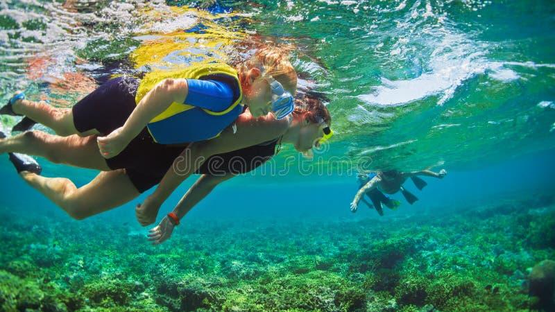 Rode overzees, vissen, gestreepte vissen, Pterois volitans Gelukkige familie die in tropische overzees snorkelen royalty-vrije stock foto