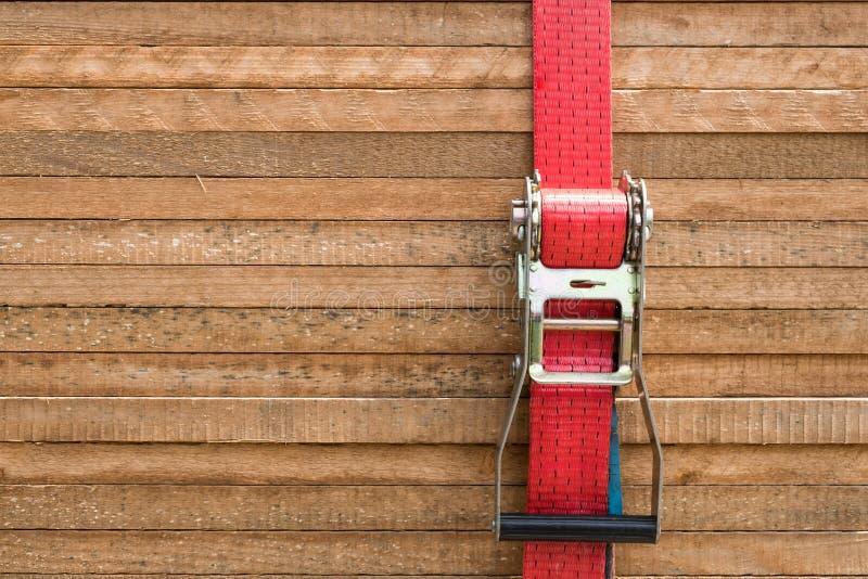 Rode palriem die houten raad/houten planken bevestigen stock afbeelding