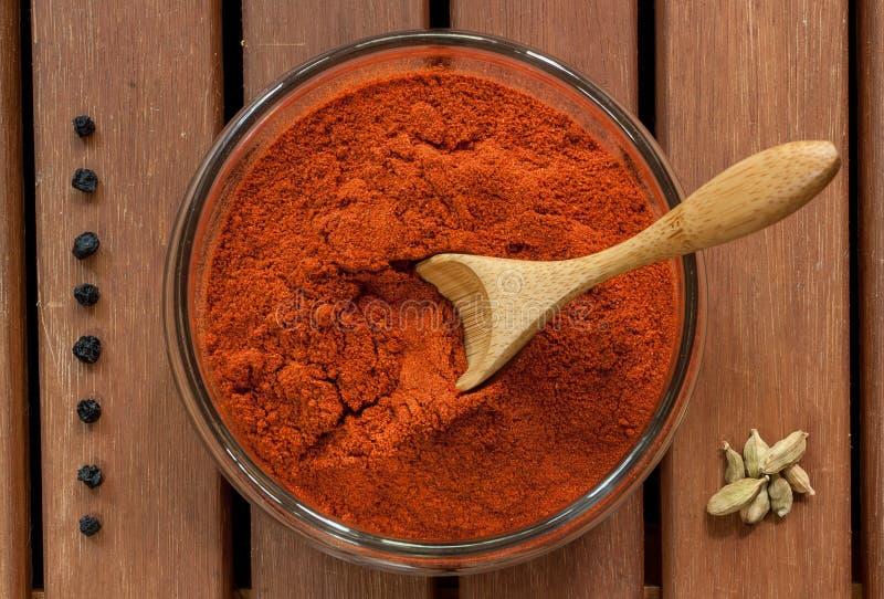 Rode paprika in een glas op een houten lijst stock foto's