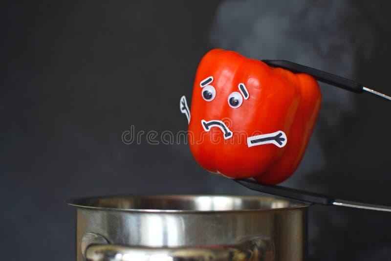 Rode Paprika met droevige gezicht en beschermende brilogen die in een stomende kokende pot op zwarte achtergrond worden gezet stock foto's