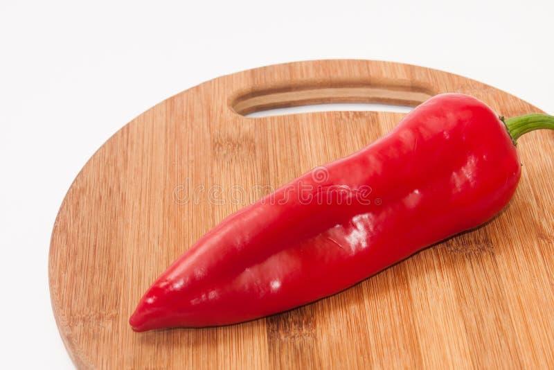 Rode paprika op de keuken houten scherpe raad stock foto's