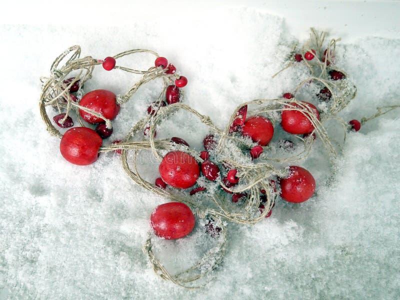 Rode parels op een sneeuw stock afbeeldingen
