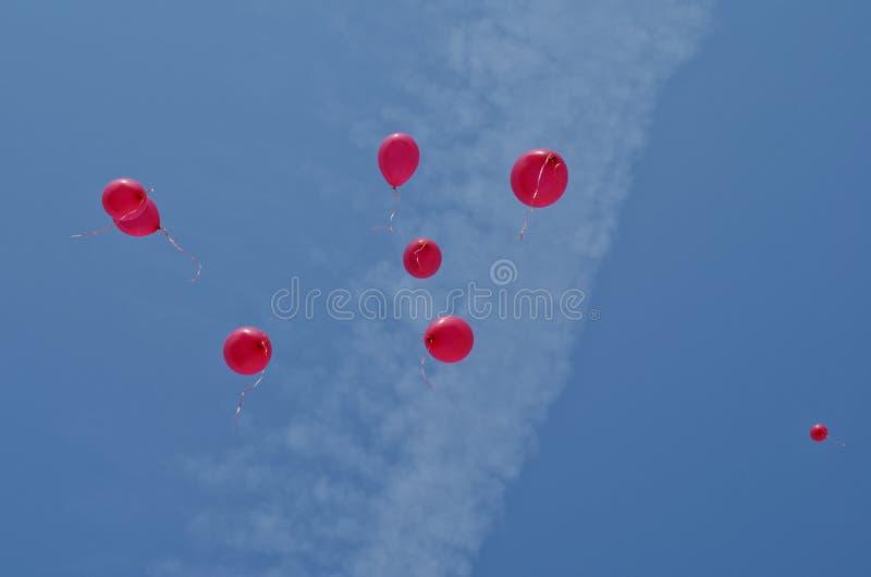 8 rode partijballons die in de blauwe hemel drijven royalty-vrije stock afbeelding