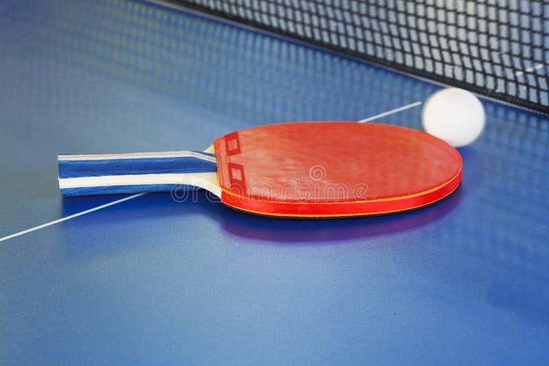 Rode peddel, tennisbal op blauwe pingponglijst royalty-vrije stock foto's