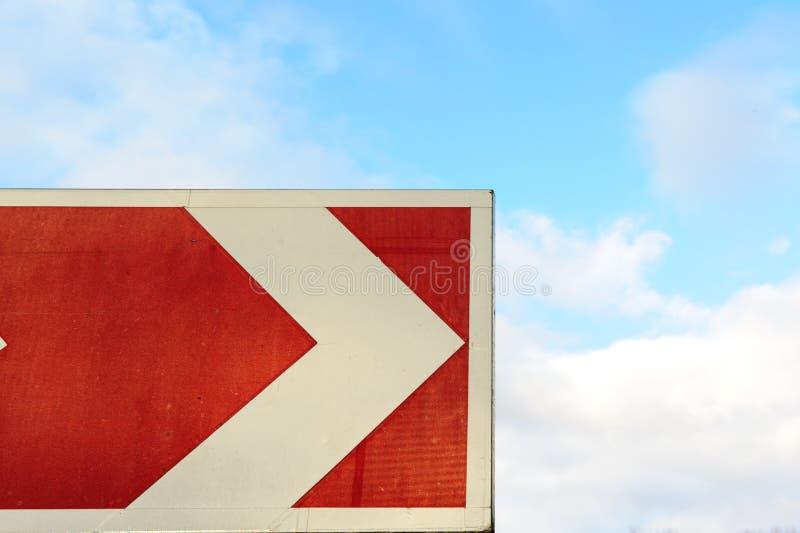 Rode pijlwijzer op hemelachtergrond Kant van de weg met en bewolkte hemel Het teken van de wegdraai De reisconcept van de de zome stock foto's