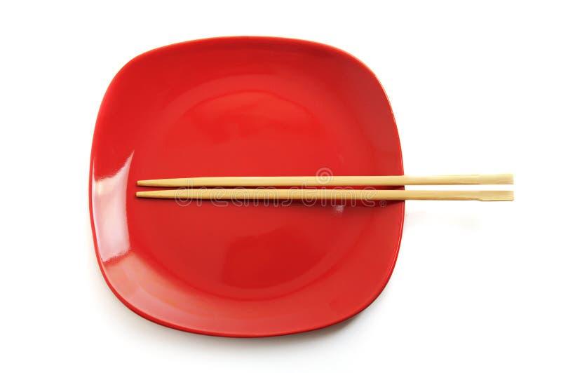 Rode plaat met Chinese stokken stock foto's