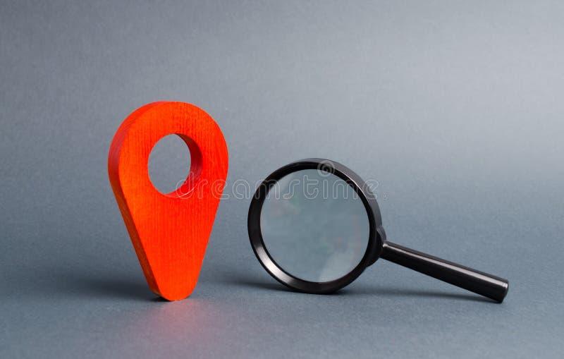 Rode plaatswijzer en een Vergrootglas op een grijze achtergrond Concept navigatie en trefpunt met nadruk op de Verrekijkers spyin stock fotografie