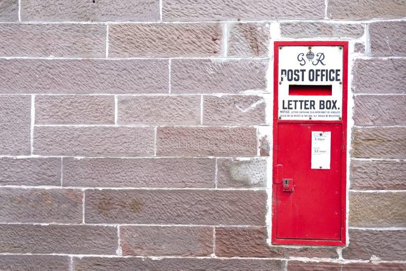 Rode postbrievenbus uitstekende retro in landelijk het plattelandsdorp van de steenmuur royalty-vrije stock foto