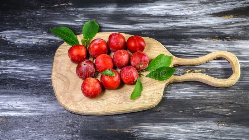 Rode pruimen met bladeren op een houten raad De dadelpruimsalade van de vitamineherfst Het op dieet zijn en gewichtsverliesconcep royalty-vrije stock afbeelding