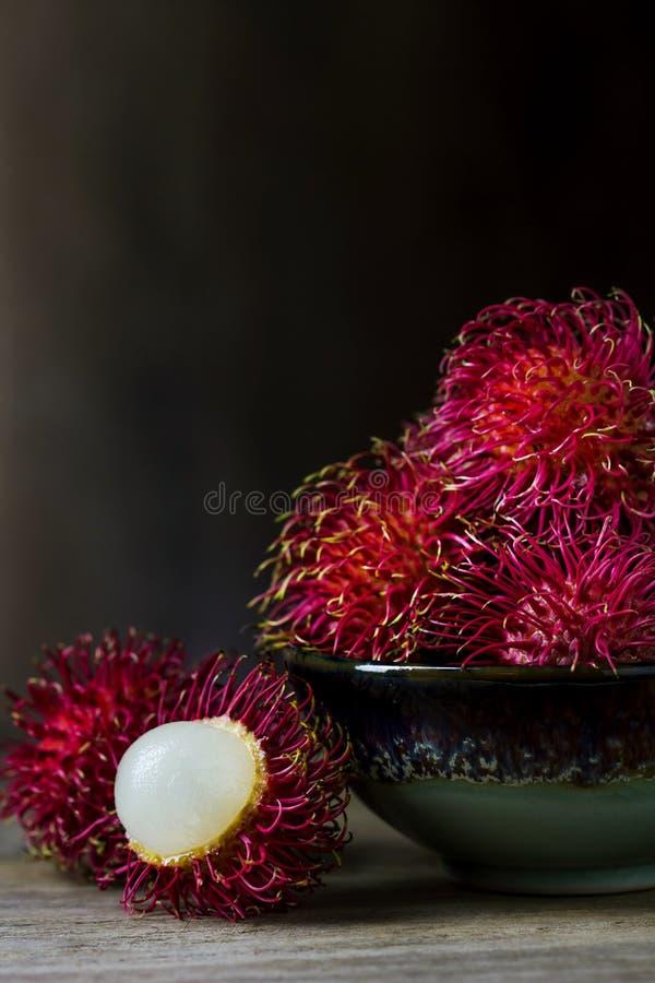 Rode rambutan in ceramische kom stock foto