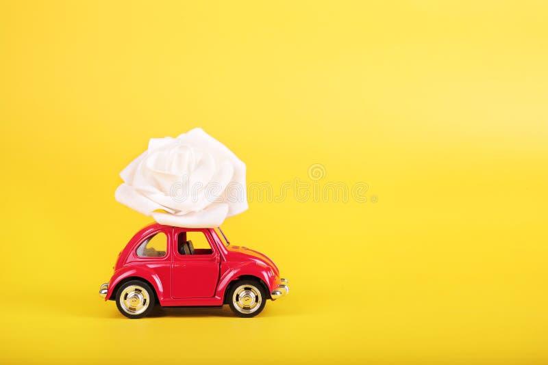 Rode retro stuk speelgoed auto met witte roze bloem op gele achtergrond Bloemen, het concept van de giftenlevering royalty-vrije stock foto
