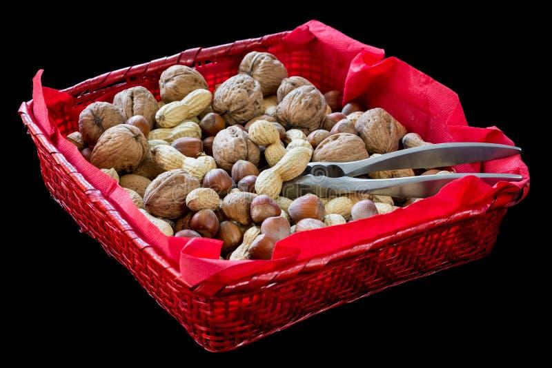 Rode rieten mand met gedroogd fruit, hazelnoot, okkernoot, amandel, pinda's en een notekraker stock foto's