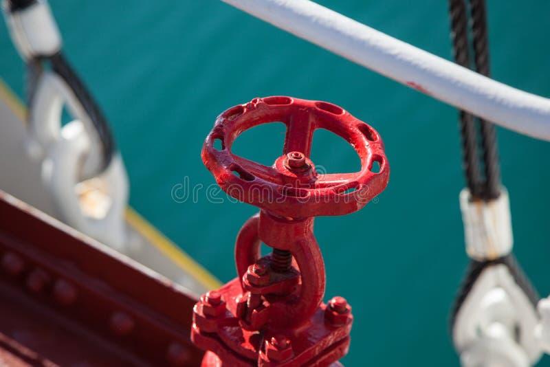 Rode roterende klep tegen blauwe zeewaterachtergrond stock afbeeldingen
