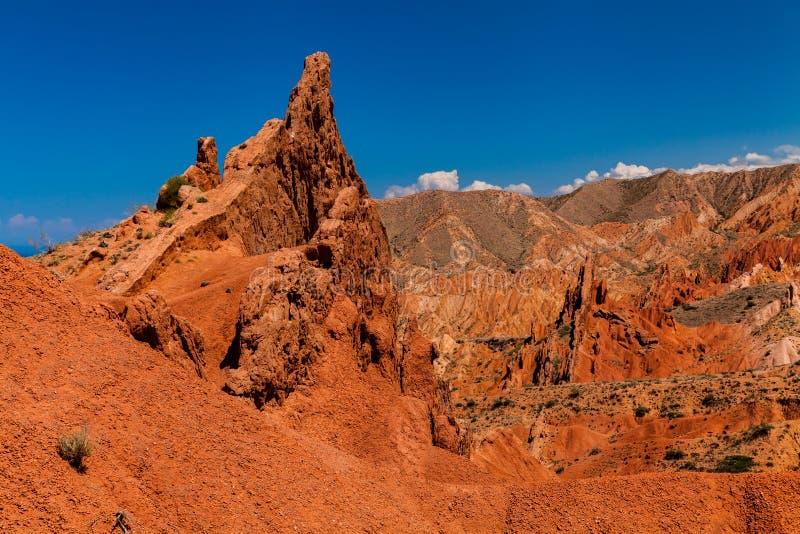 Rode rotsen onder de blauwe hemel in de canion Skazka, Kyrgyzstan stock fotografie