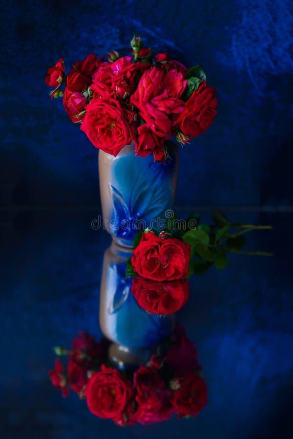 Rode rozebottel in een blauwe vaas royalty-vrije stock afbeelding