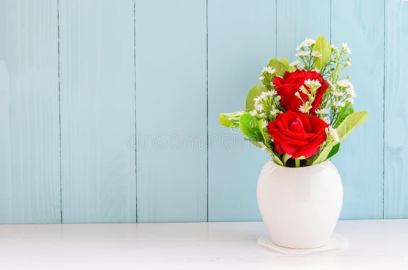 Rode rozen bij witte vaas stock afbeelding