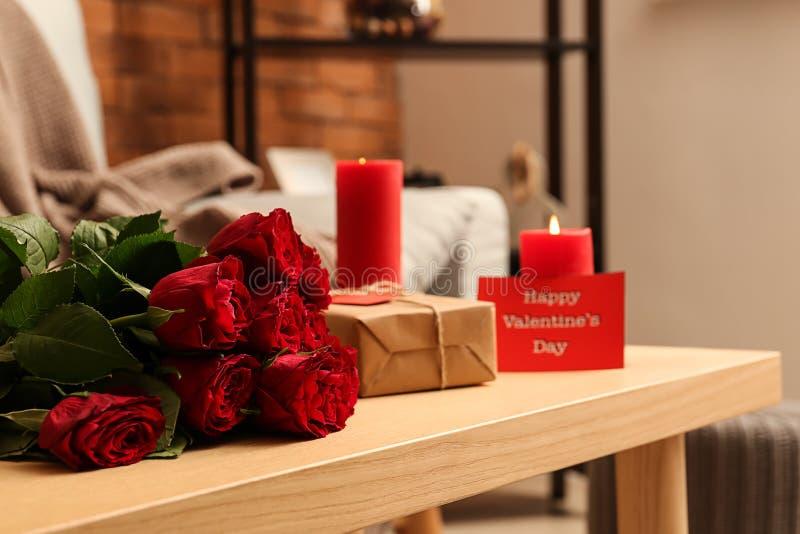 Rode rozen met gift en brandende kaarsen op houten lijst De Viering van de valentijnskaartendag stock foto's