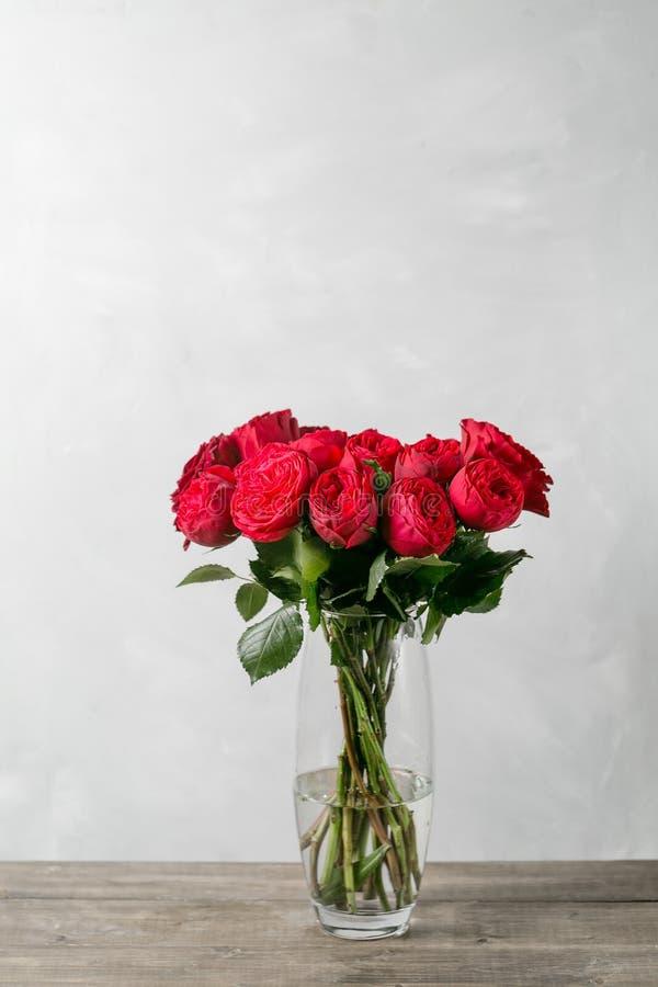 Rode rozen in vaas op houten lijst de Rode Piano van de tuinpioen royalty-vrije stock fotografie