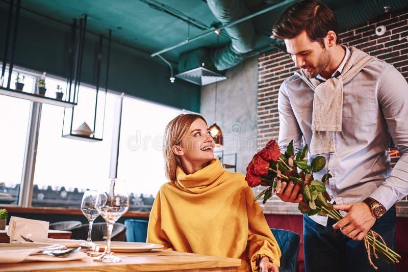 Rode rozen voor vrouw De mens in blauw overhemd verraste zijn mooi blondemeisje stock foto