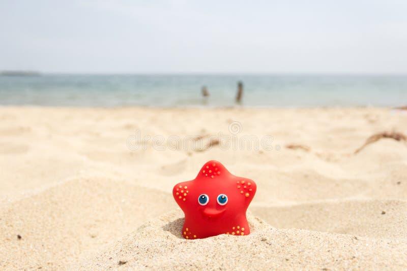 Rode rubberstuk speelgoed ster op zandstrand bij de kust en de jonge geitjes die in het overzees op achtergrond spelen royalty-vrije stock afbeelding
