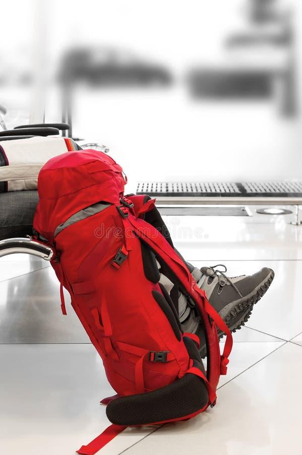 Rode rugzak met een reiziger bij de luchthaven die op uw vlucht wachten reis concept Backpackerstijl Vage achtergrond royalty-vrije stock afbeeldingen