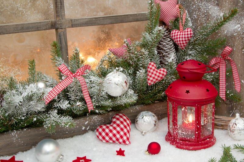 Rode rustieke Kerstmisdecoratie op venstervensterbank met gecontroleerd rood royalty-vrije stock foto
