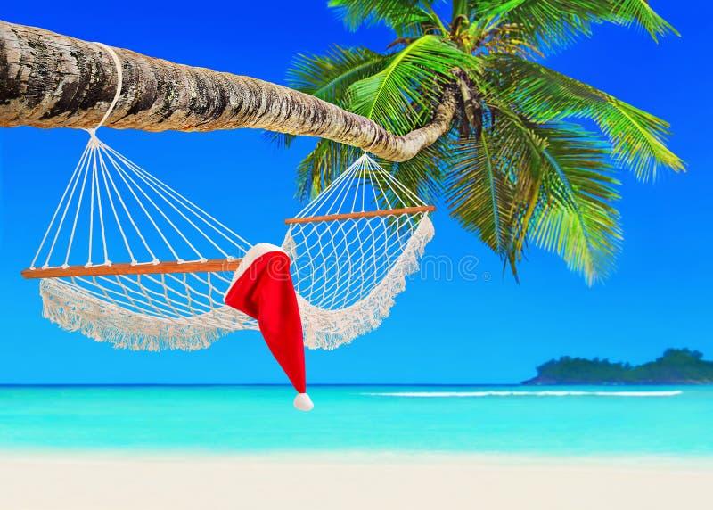 Rode Santa Claus-hoed op hangmat bij het strand van het palmeiland stock afbeelding