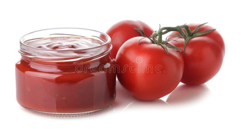 Rode saus in een kruik en verse ingrediënten, tomaten op een wit geïsoleerde achtergrond Eigengemaakte tomatensaus ketchup royalty-vrije stock foto